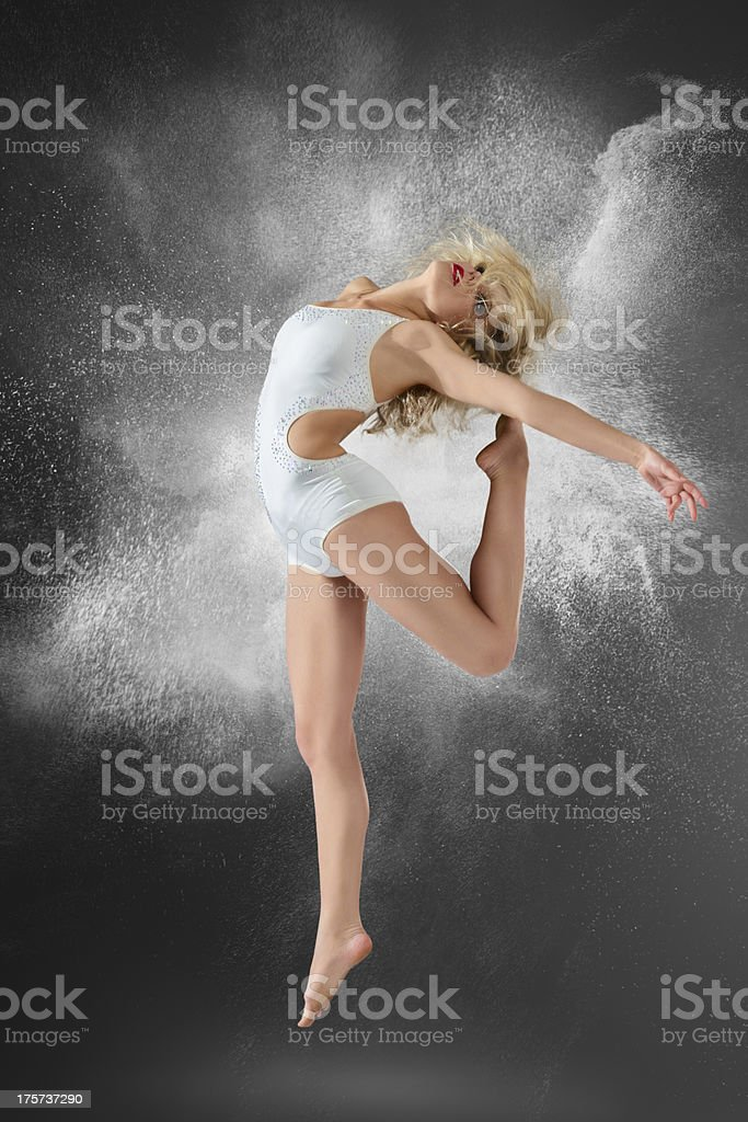 Dancer jumping into white powder cloud royalty-free stock photo