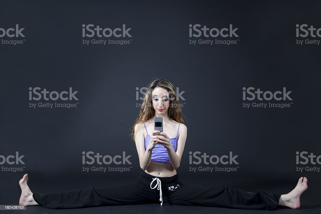 dancer stretching sitting with legs apart, texting royalty-free stock photo