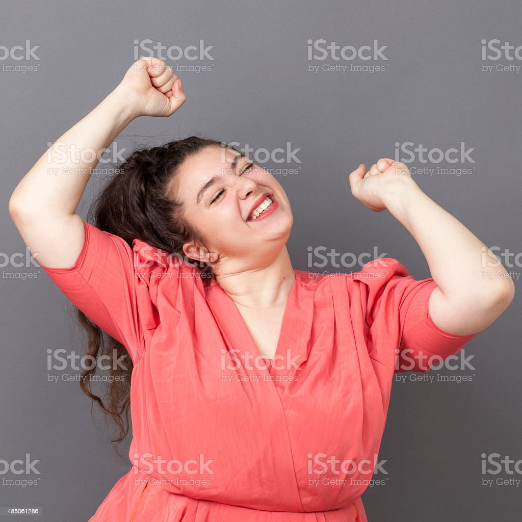 dancing 20s big woman expressing joy and success stock photo