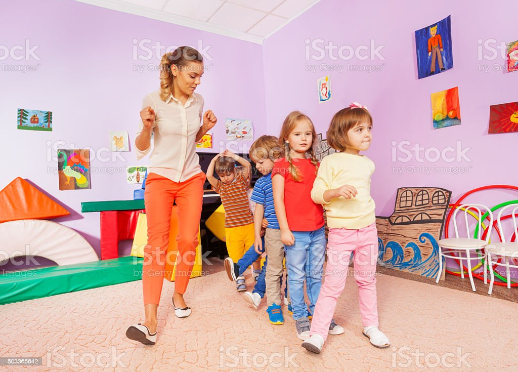 Dancing lesson with kids repeat after teacher stock photo