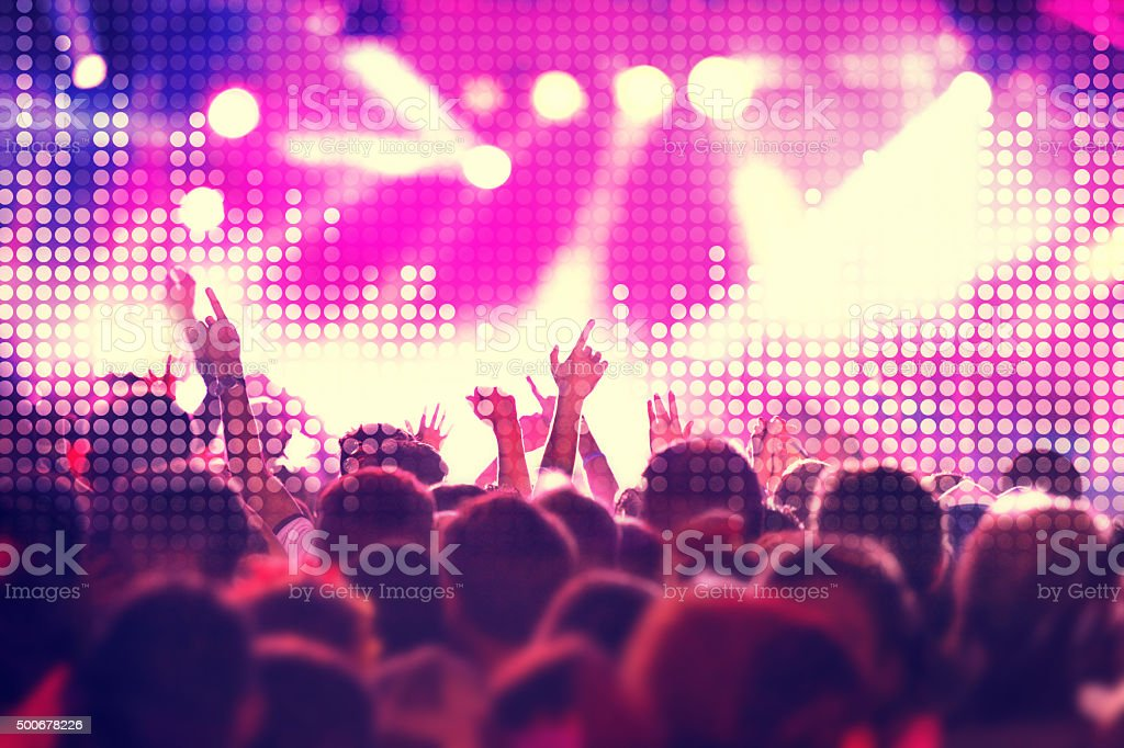 Dancing people with arms raised at concert, equalizer sound wave stock photo