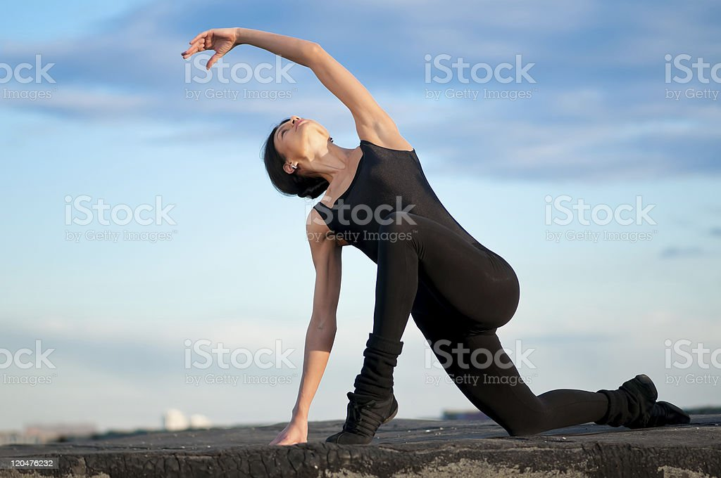 dancing woman over blue sky. Yoga royalty-free stock photo