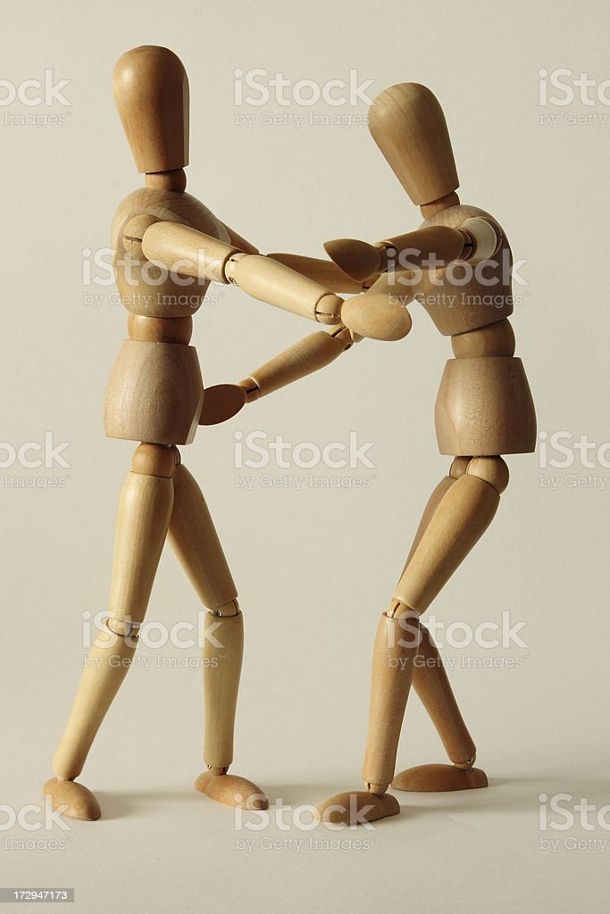 Dancing wooden dummies on white background royalty-free stock photo