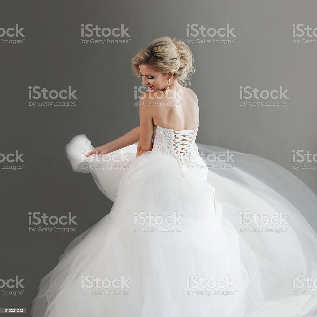 Dancing young bride in luxurious wedding dress. Pretty girl in stock photo