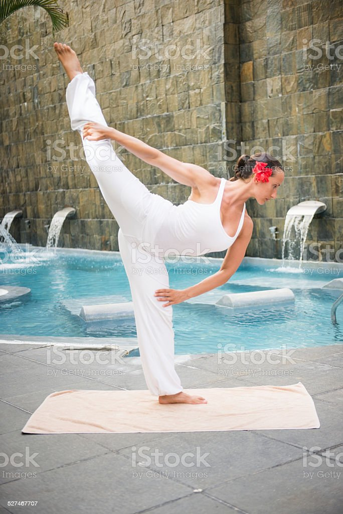 Dandayamana dhanurasana pose - woman exercising yoga stock photo
