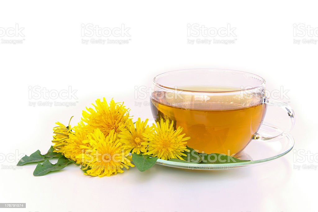 Dandelions laying next to tea served in glassware stock photo