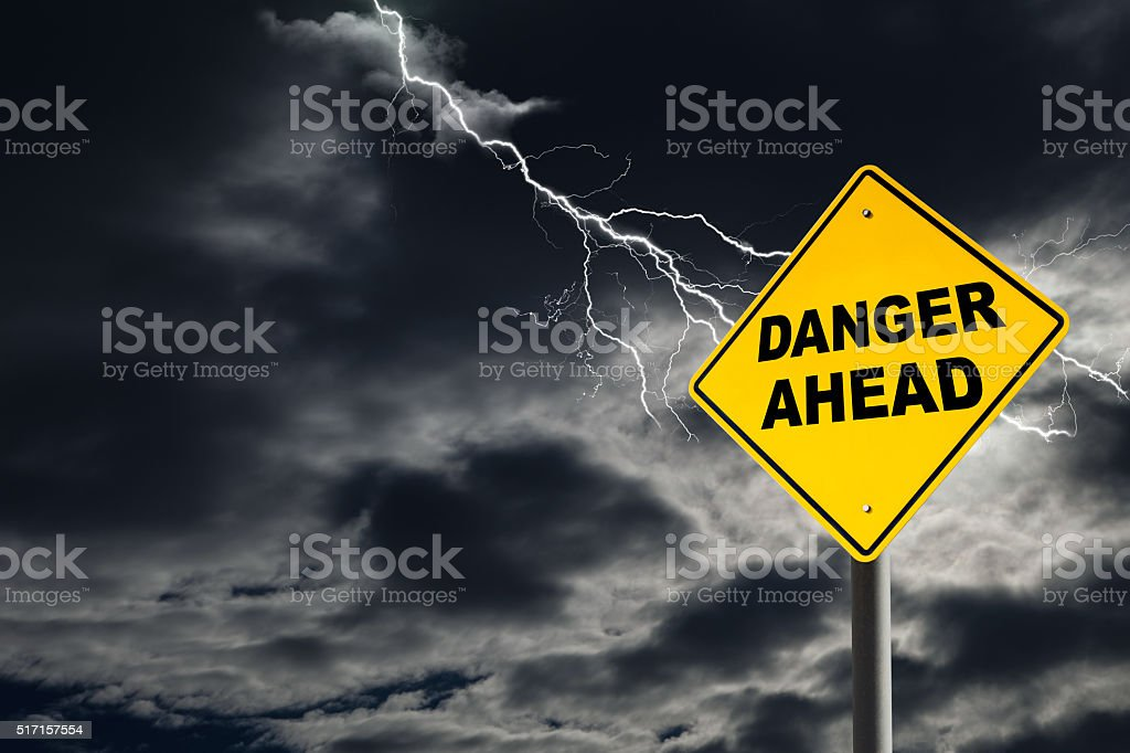 Danger Ahead Sign Against Cloudy and Thunderous Sky stock photo