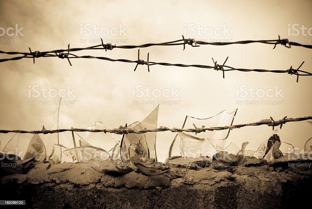 danger - barbed wire and broken bottles stock photo