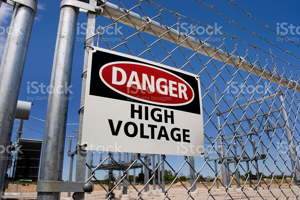 Danger high voltage sign on a fence royalty-free stock photo