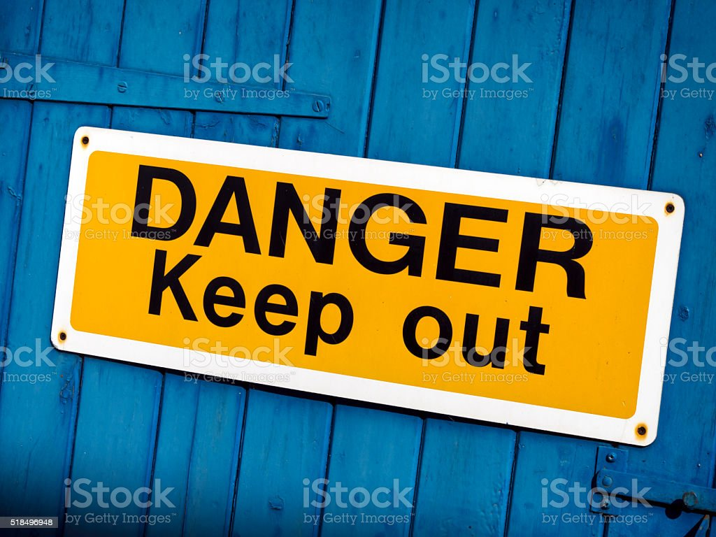'Danger Keep Out' sign on a blue gate stock photo