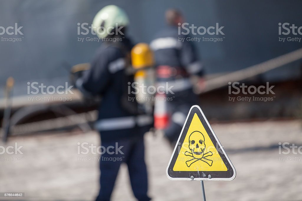 danger sign with skull and crossbones, firefighters on background stock photo