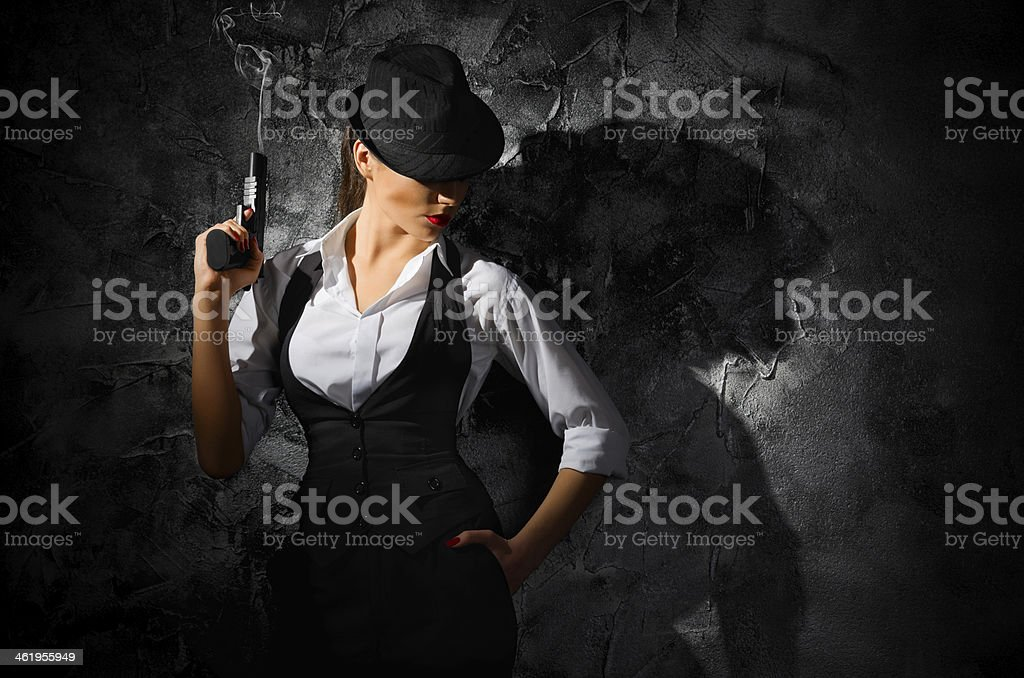 Dangerous and beautiful criminal girl with gun stock photo