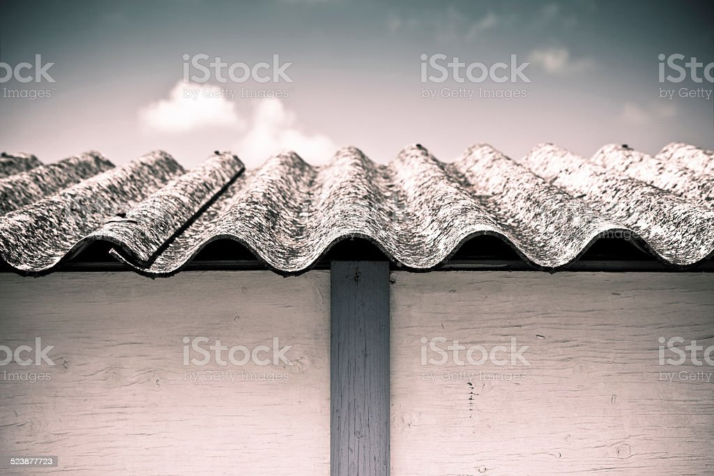 Dangerous asbestos roof - toned image with copy space stock photo