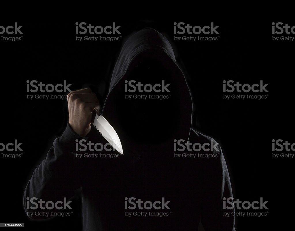 Dangerous hooded man holding knife stock photo