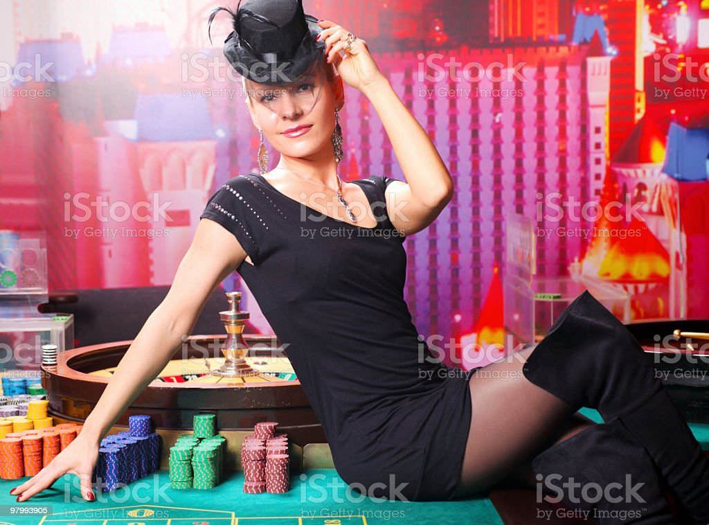 Dangerous lady sitting on the casino table. stock photo