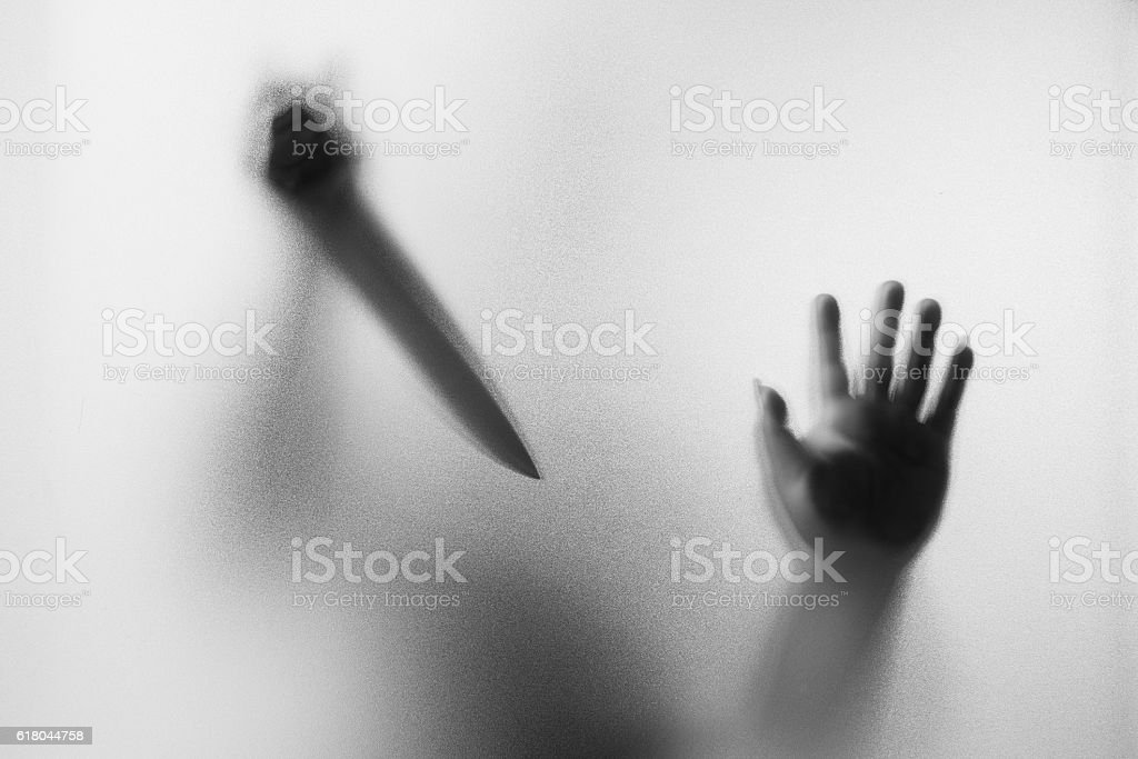 Dangerous man behind the frosted glass with a knife stock photo