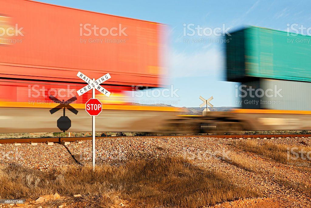 Dangerous railway crossing safety sign with double-stack freight train stock photo