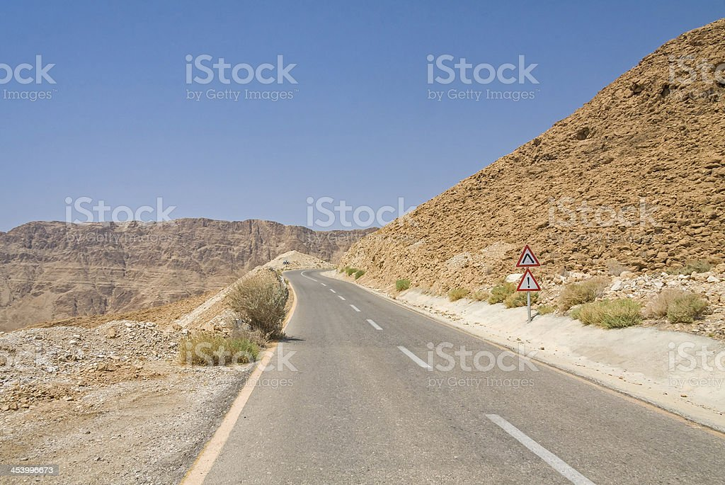 Dangerous road sign on steep turn of ascend highway royalty-free stock photo