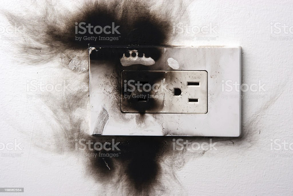 A dangerous situation shown with a burnt electronical socket stock photo