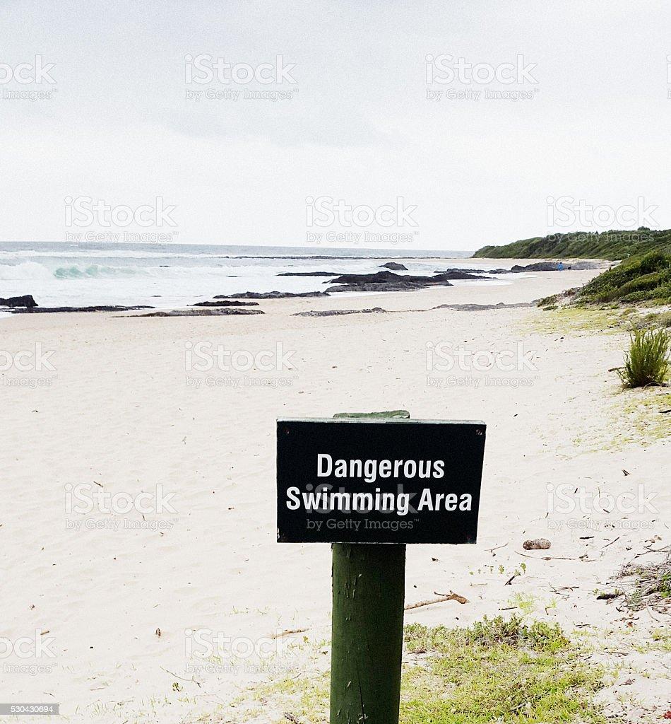 'Dangerous Swimming Area' sign on deserted beach stock photo