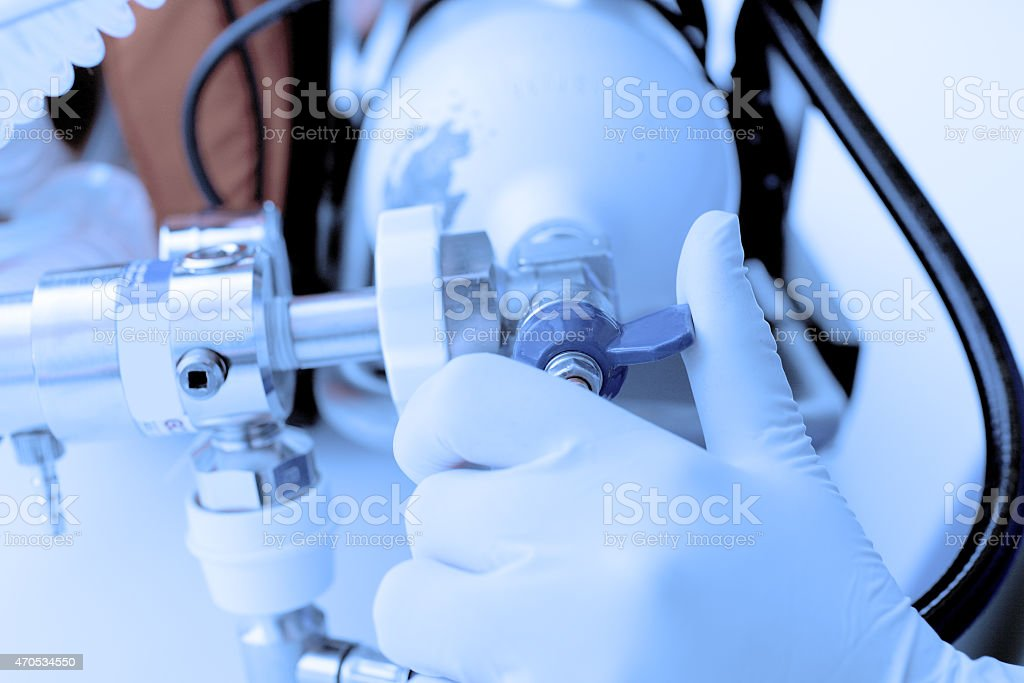 dangerous workplace. hand in protective glove rotates valve of balloon. stock photo