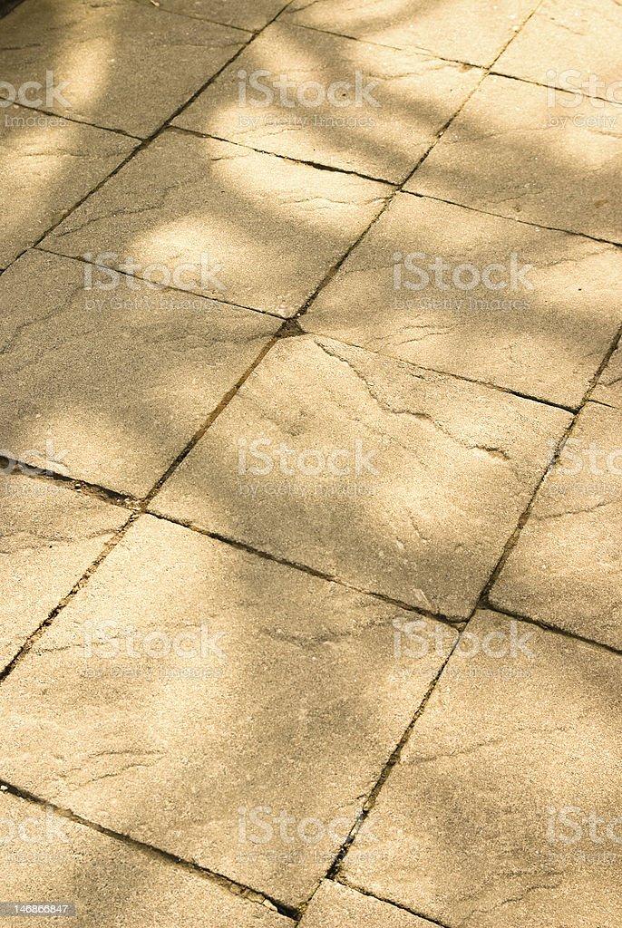 Dappled light on stone texture of path royalty-free stock photo