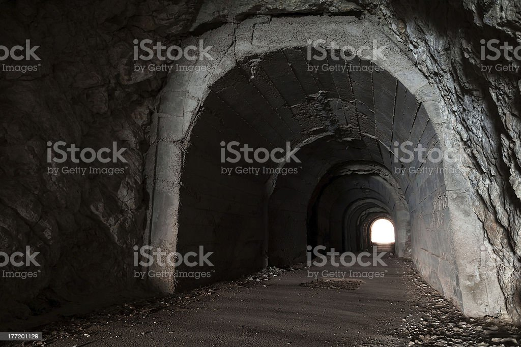 Dark abandoned tunnel interior perspective with glowing end royalty-free stock photo