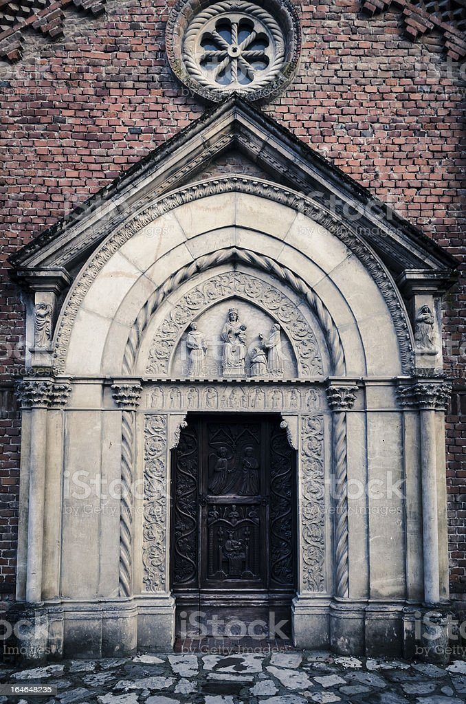 Dark ancient church front door with marble statues royalty-free stock photo