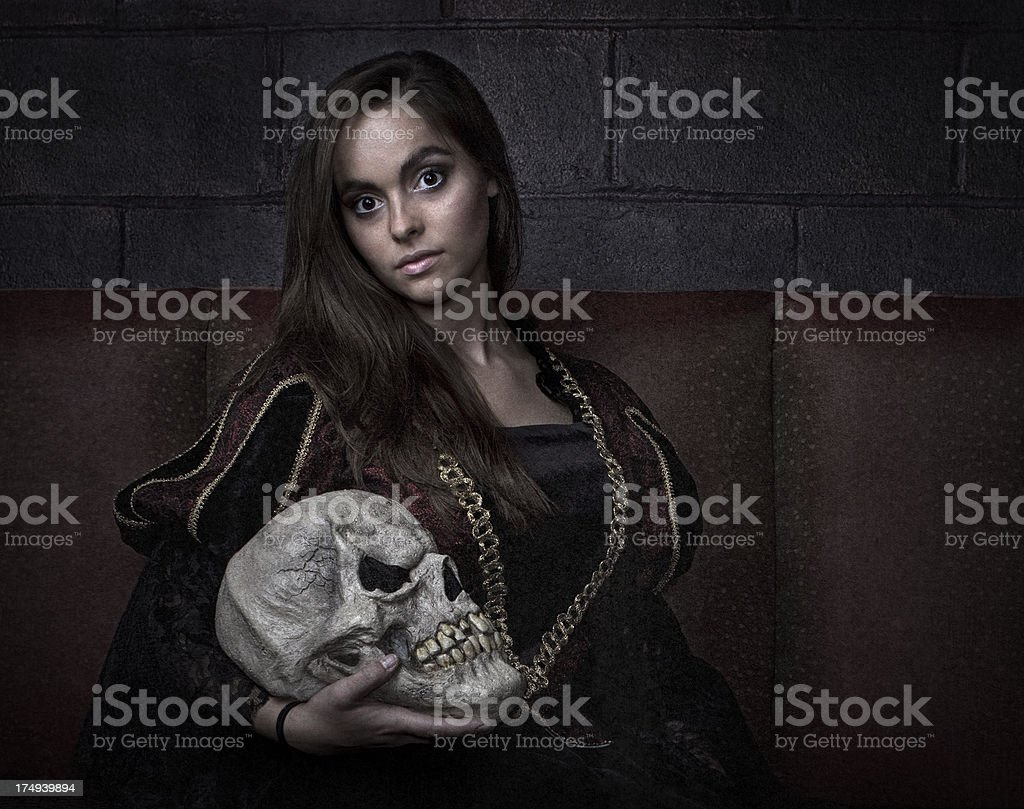 Dark and Beautiful Young Woman Holding Skull royalty-free stock photo