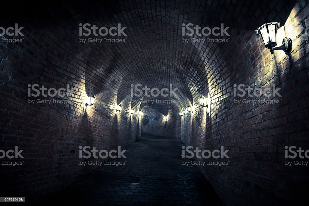 Dark and damp lamplit underground tunnel, Alba Iulia, Transylvania, Romania stock photo