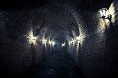 Dark and damp lamplit underground tunnel, Alba Iulia, Transylvania, Romania