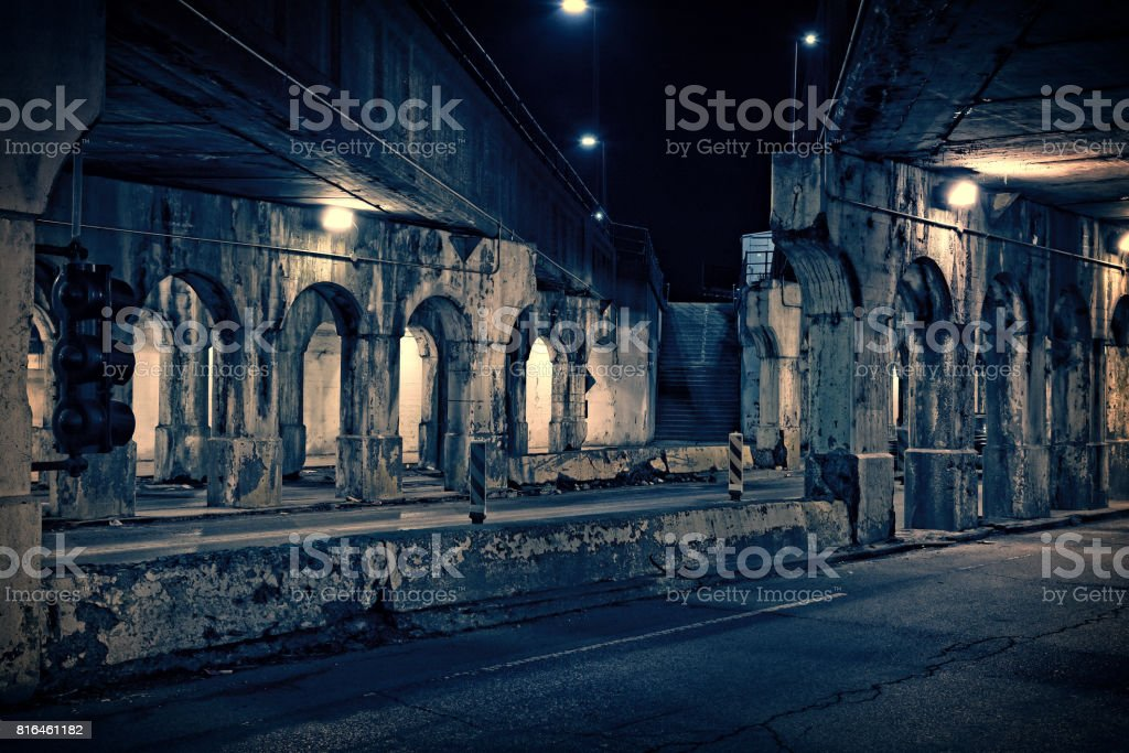 Dark and gritty Chicago urban city street at night. Decaying train bridge underpass with stairs to elvated train station. stock photo