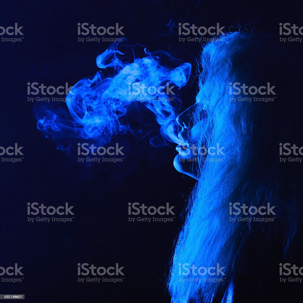 dark and sullen shot of a young woman smoking stock photo