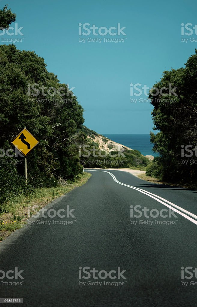 Dark and winding Australian coastal road with warning sign royalty-free stock photo