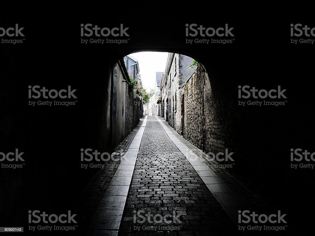 Dark Arched Alleyway over ancient cobbled road royalty-free stock photo