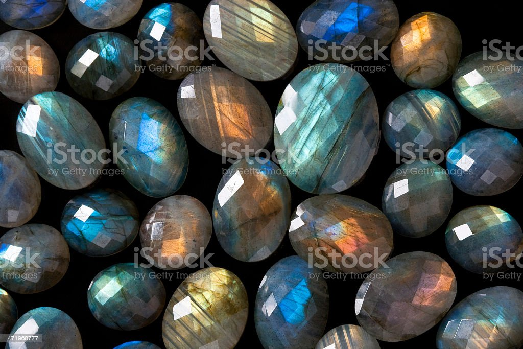 Dark beautiful gemstones background: many faceted colorful labradorite gems. stock photo