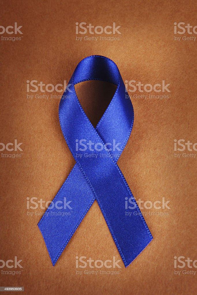 Dark Blue Awareness Ribbon on Brown stock photo