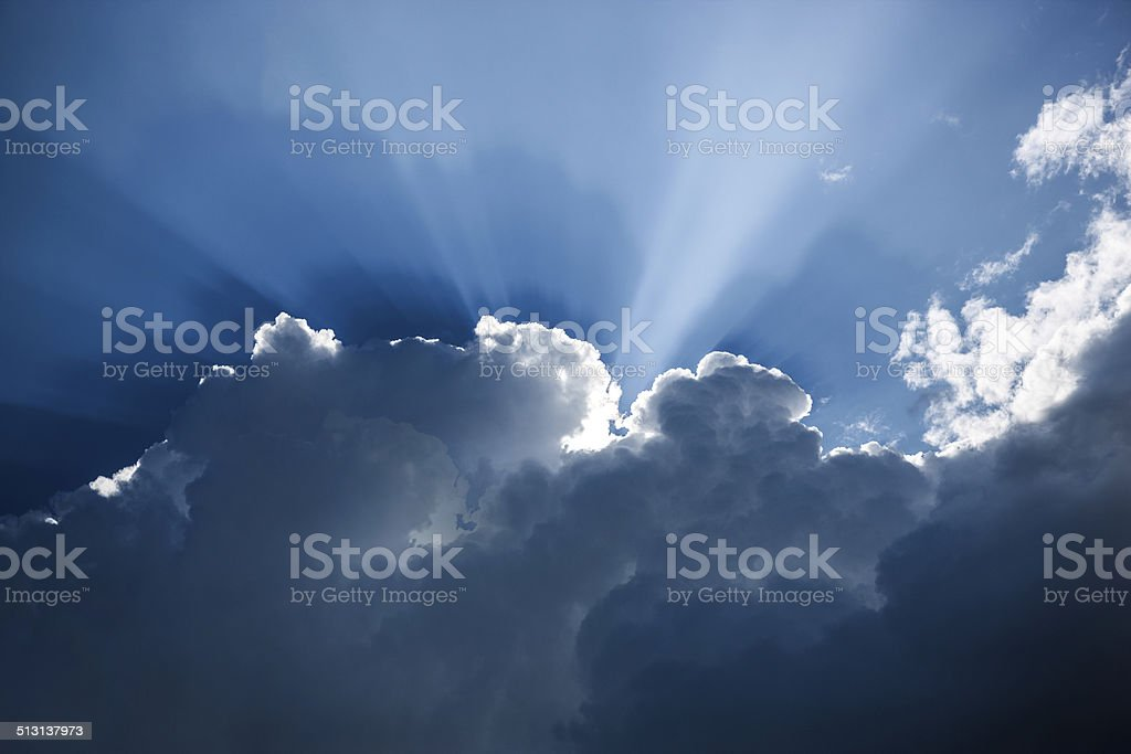 Dark blue cloud formation with sunbeams royalty-free stock photo