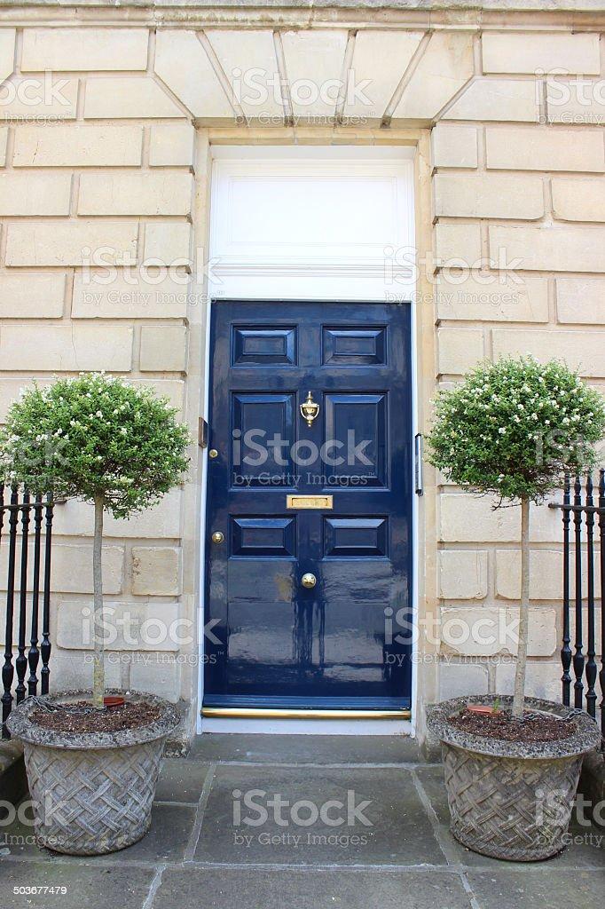 Dark blue front door on Georgian house, standard bay trees stock photo