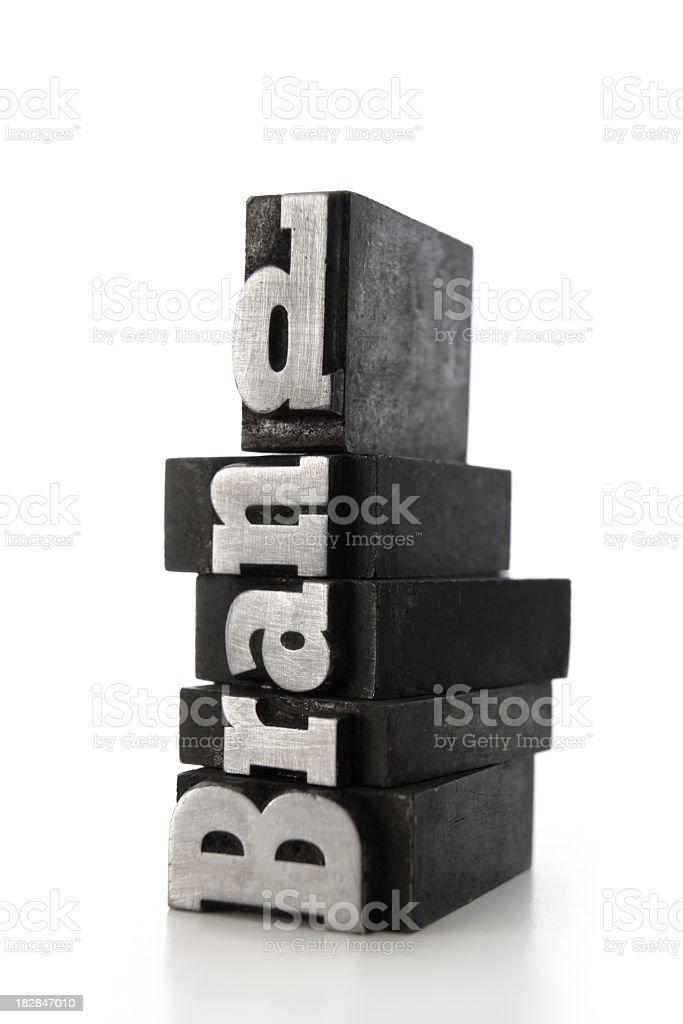Dark bricks with a letterpress that spells BRAND royalty-free stock photo