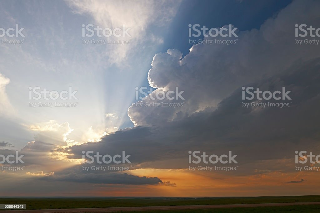 Dark, brooding storm clouds with sunrays and sunset stock photo