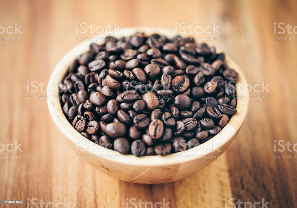 Dark brown coffee beans in a wooden bowl royalty-free stock photo