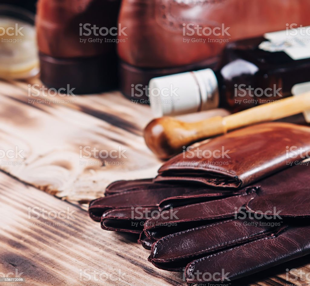 Dark brown leather wallet,oxfords shoes, bottle of whiskey and stock photo