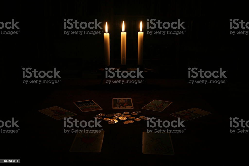 A dark candlelit room with money and tarot cards stock photo
