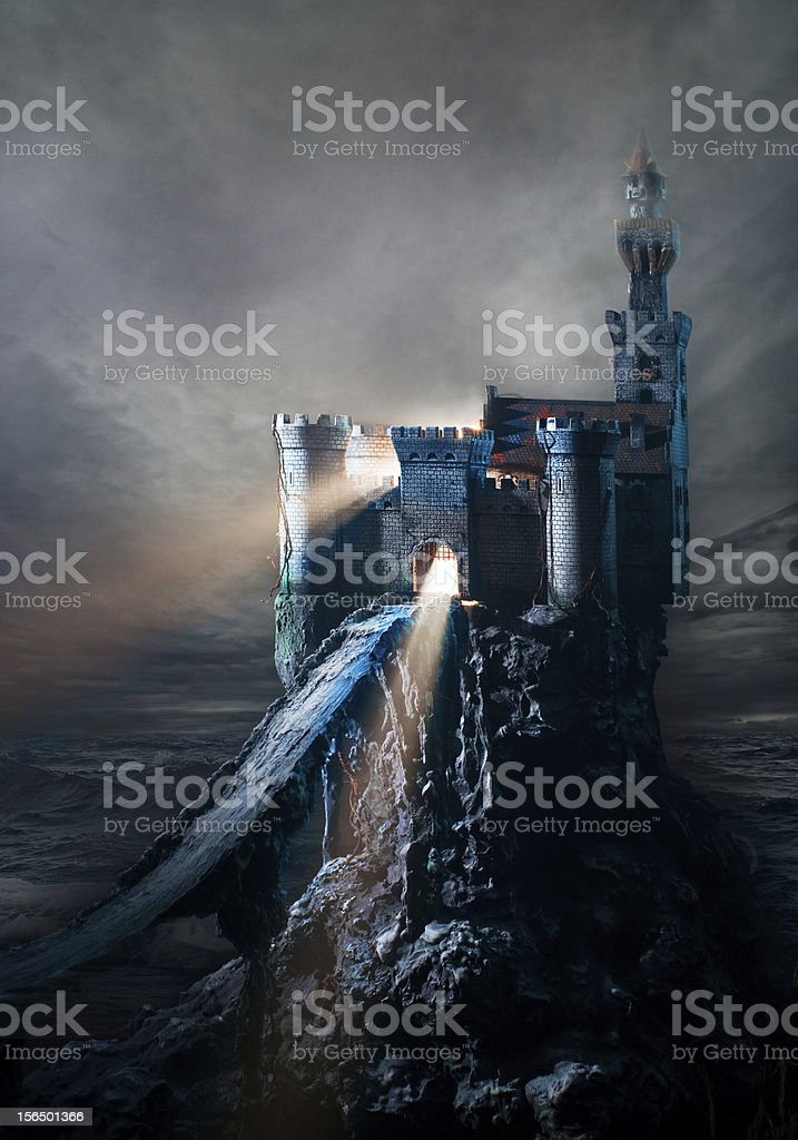 Dark castle on an isolated island with waves crashing around stock photo