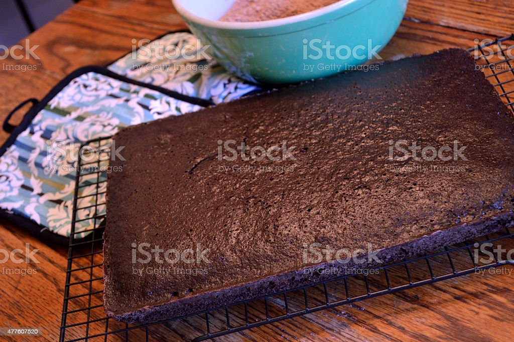 Dark chocolate cake cooling on rack on wooden table stock photo