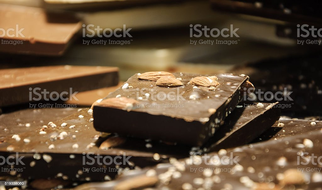 Dark chocolate with almonds. Milk and white chocolate at background. stock photo