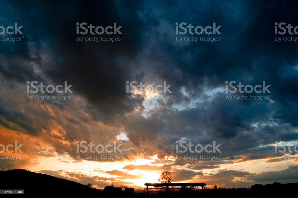 A dark cloud sky with the sun shining through royalty-free stock photo