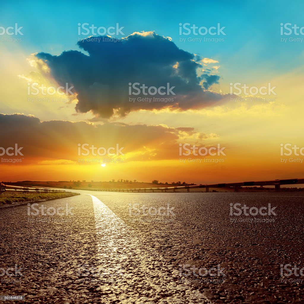 dark clouds over asphalt road on sunset stock photo