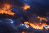 Dark clouds partially lit by evening sun